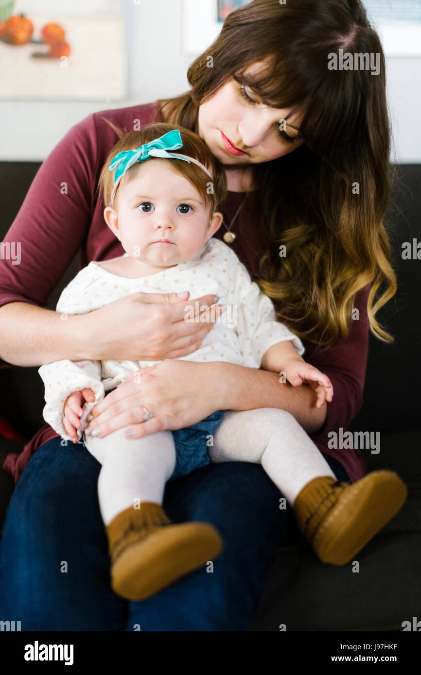Mother with daughter (12-17 months) sitting on sofa - Stock Image