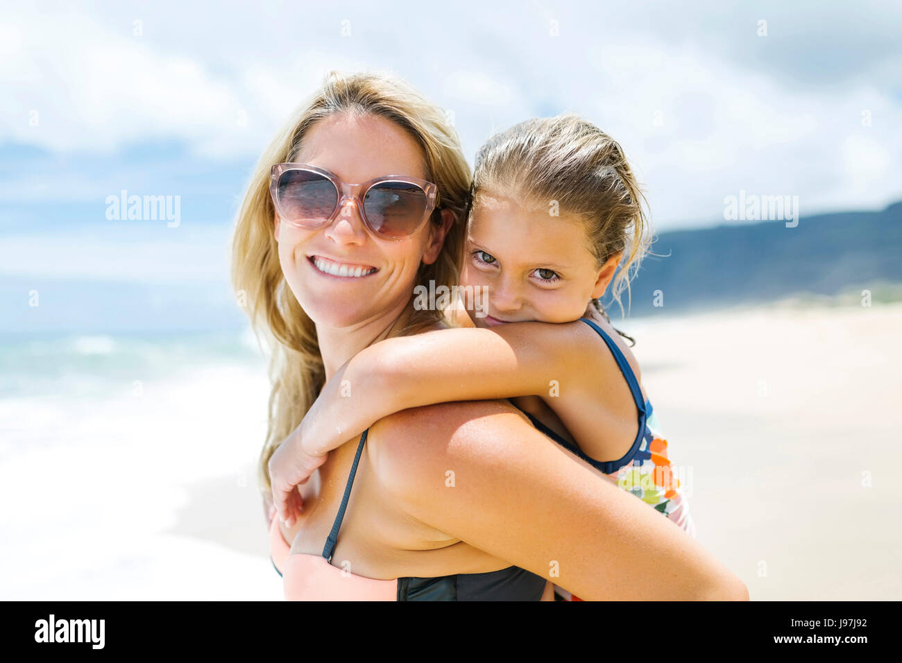 USA, Hawaii, Kauai, Mother with daughter (6-7) playing on beach - Stock Image