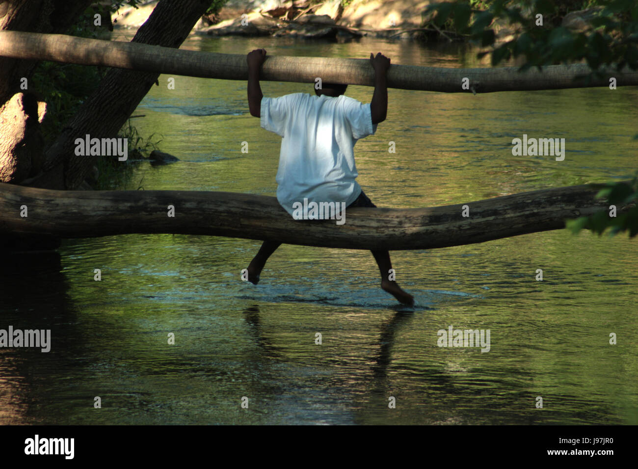 Boy alone sitting on fallen tree trunk over water - Stock Image