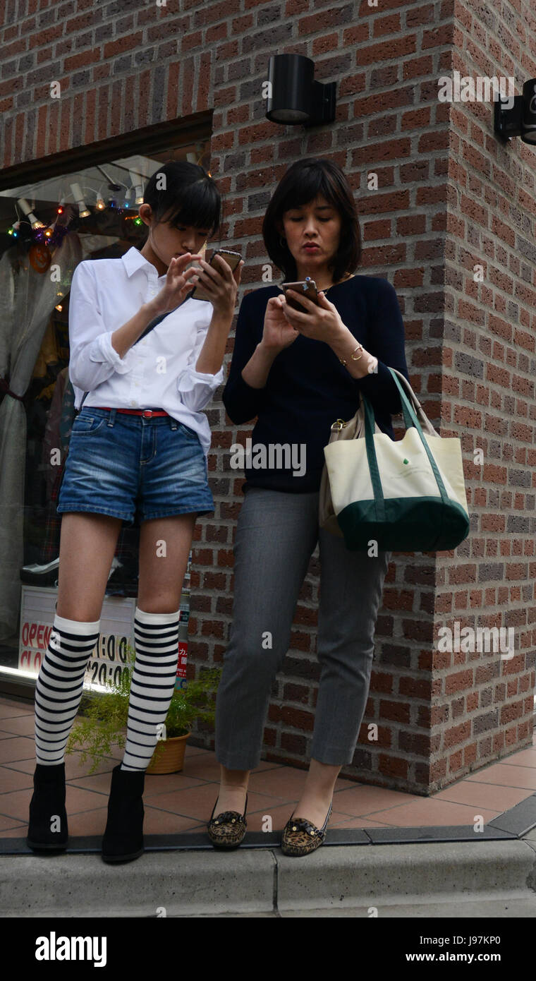 Mother & daughter using their smartphones. - Stock Image