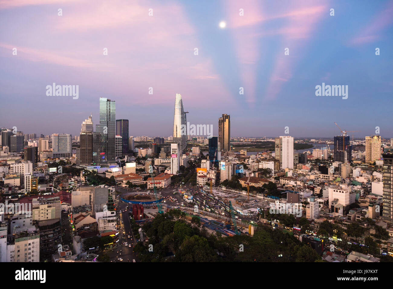 The sun sets over the Ho Chi Minh City skyline that mix the colonial and business district in Vietnam largest city, Stock Photo