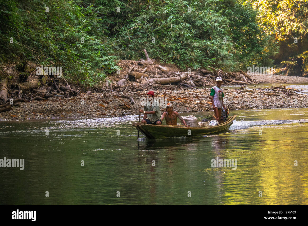Manoeuvring boat through shallow rapids in the Heart Of Borneo, West Kalimantan, Indonesia. - Stock Image