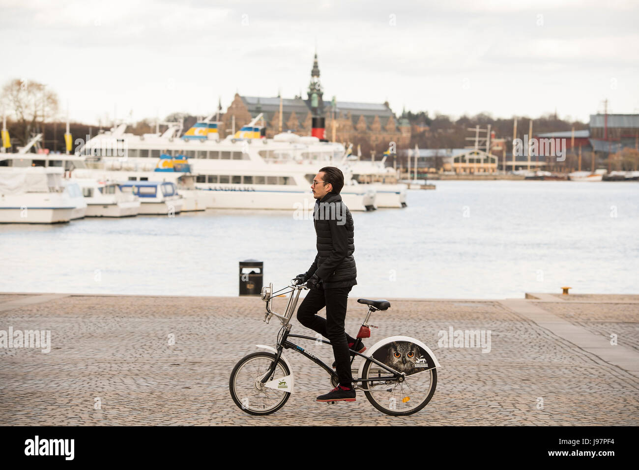 Young man on bike in Stockholm - Stock Image