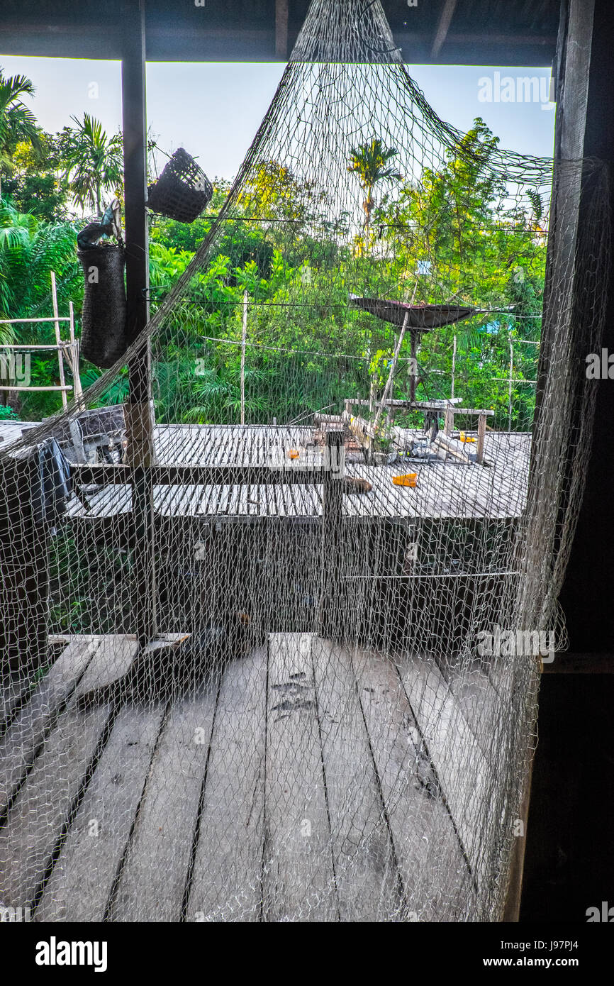 Fishing net handing from the ceiling of a longhouse in Kalimantan Borneo, Indonesia. - Stock Image