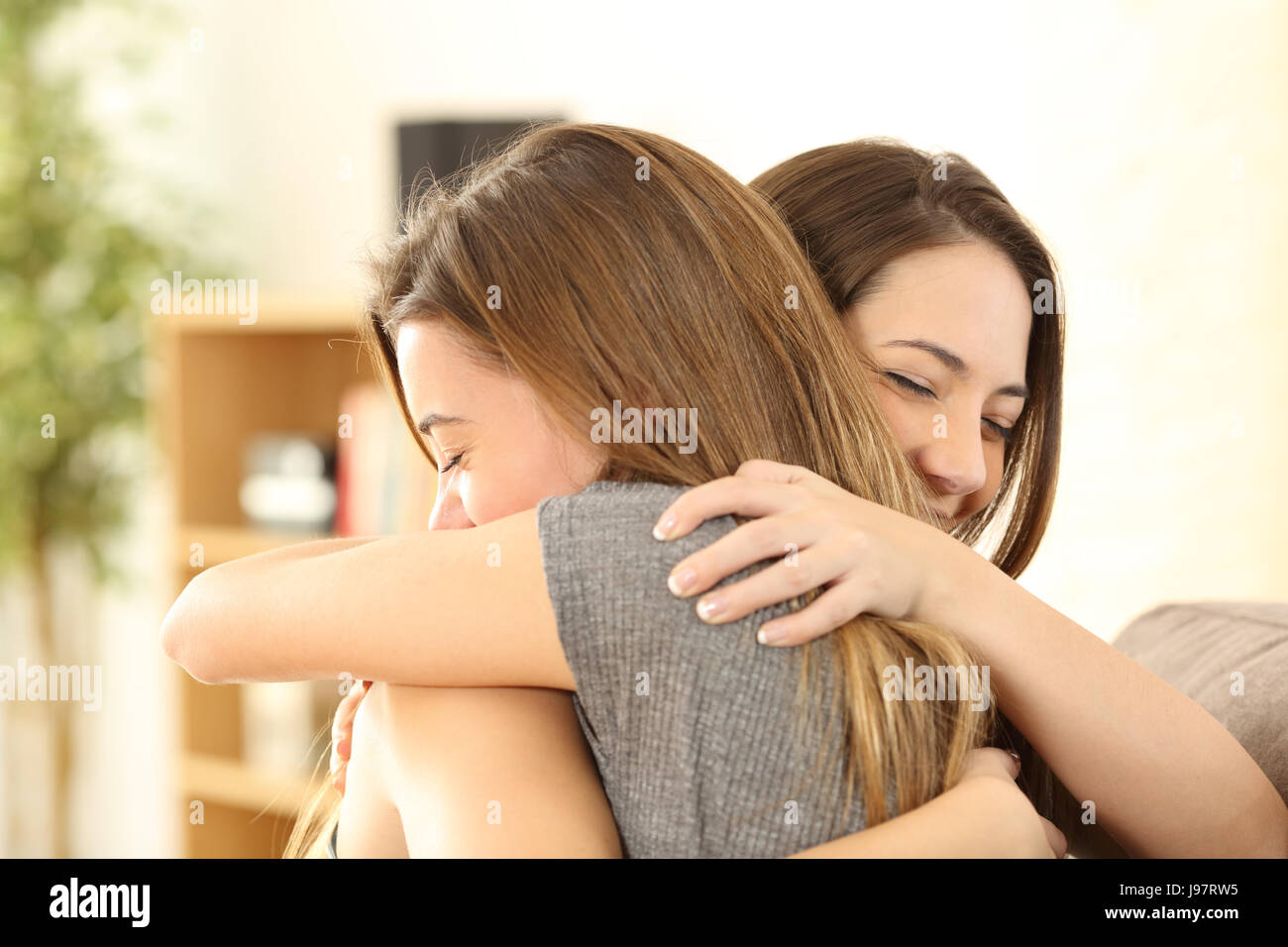 Happy girls embracing at home sitting on a couch in the living room at home - Stock Image