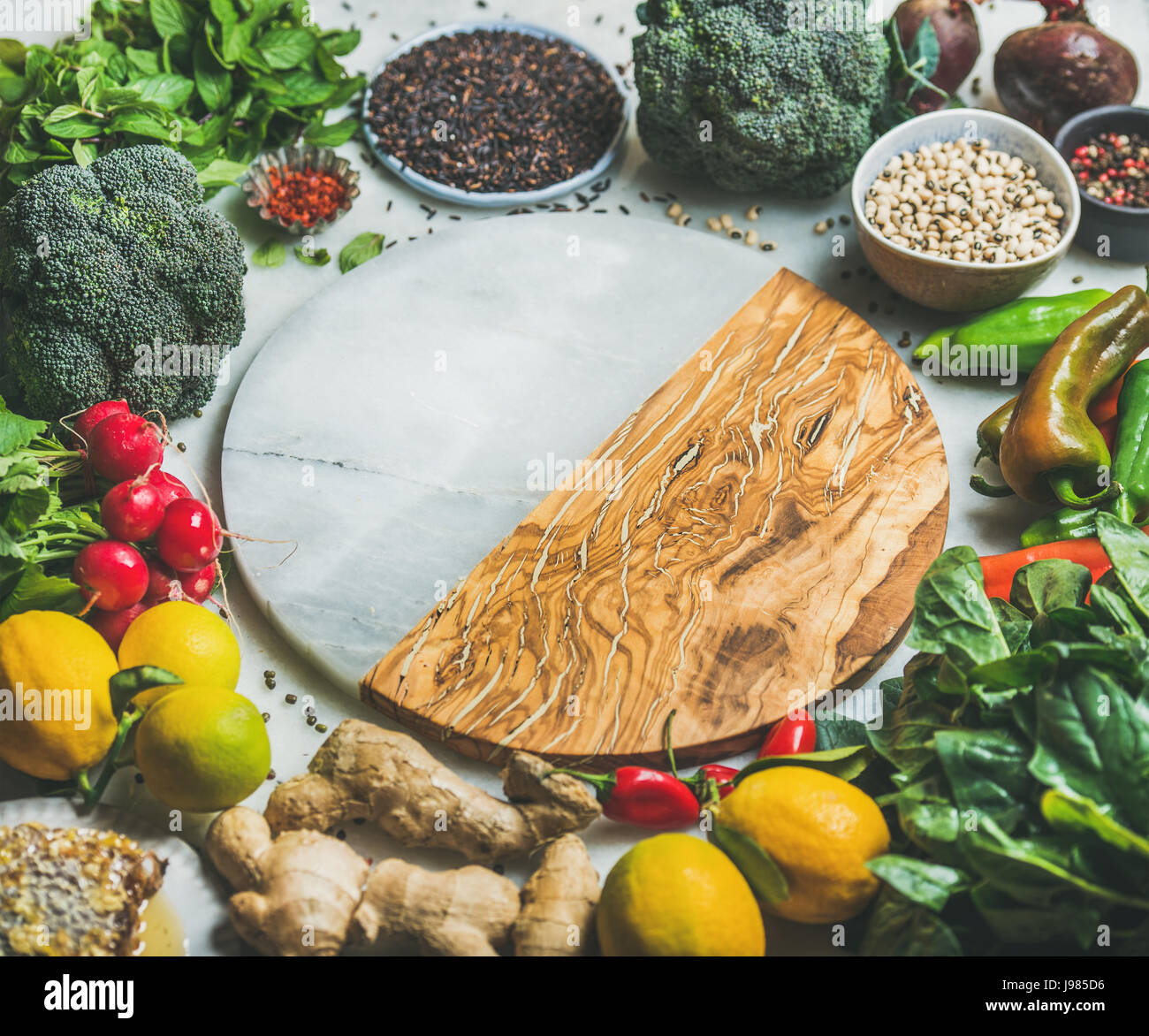 Vegetables, beans, grains, greens, fruit, spices over grey background - Stock Image