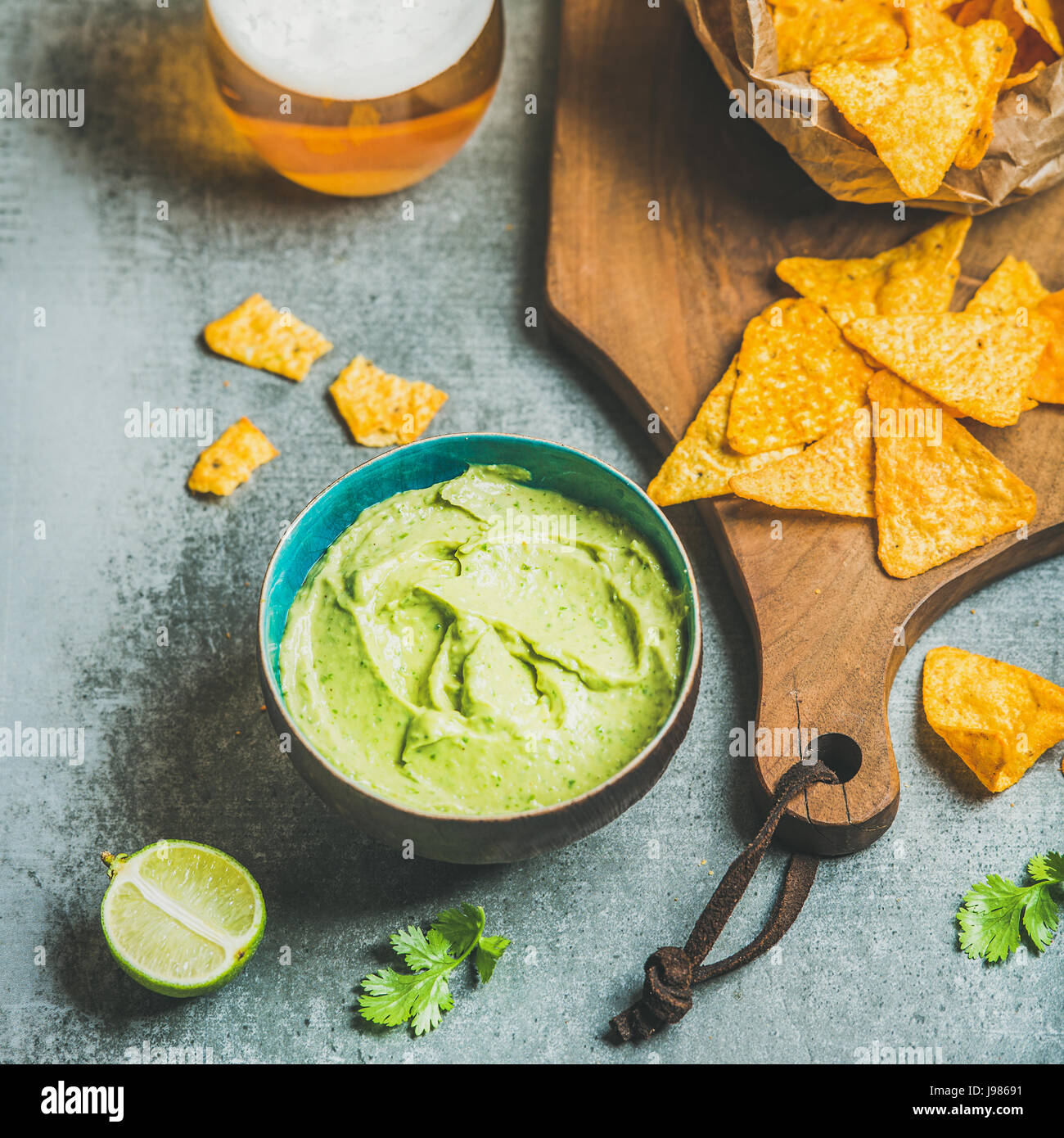 Mexican corn chips, fresh guacamole sauce and beer, square crop - Stock Image