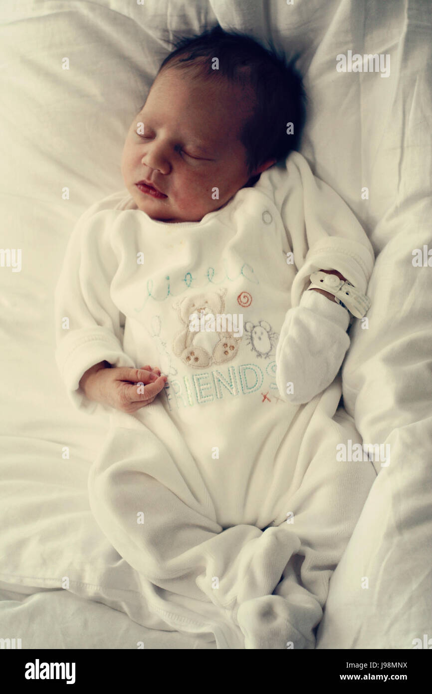 Headshot of newborn baby girl sleeping soundly with black hair