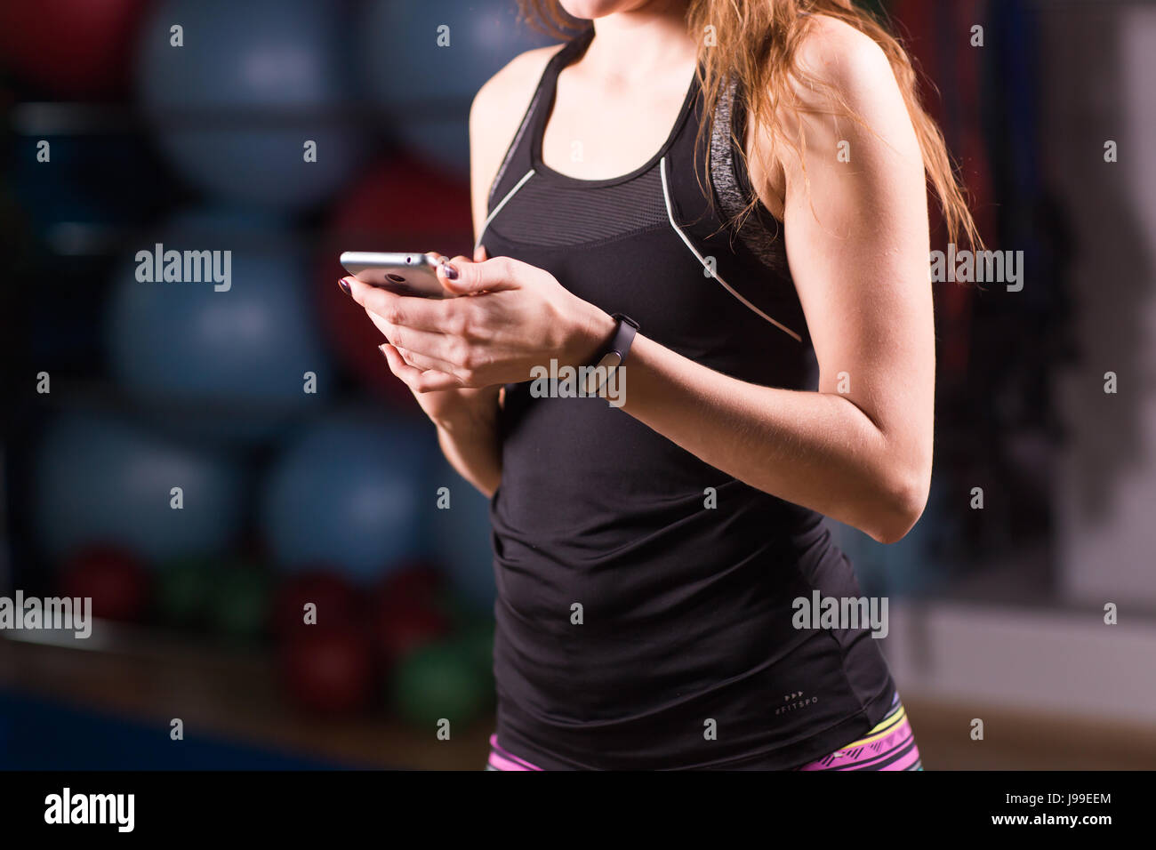 Young woman with fitness tracker and smartphone in gym. - Stock Image