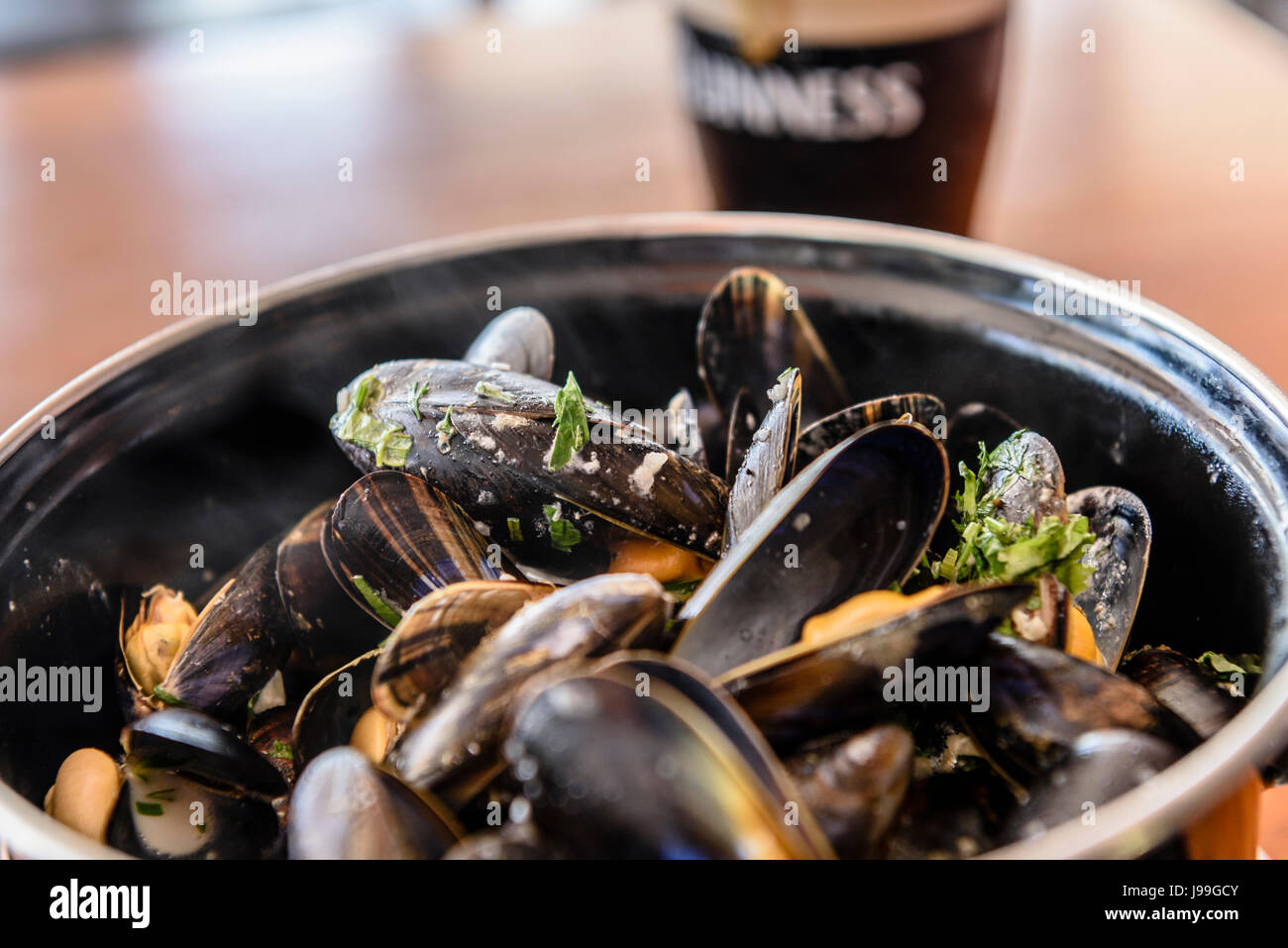 A bowl of mussels with garlic, white wine and parsley with a pint of Guinness. - Stock Image