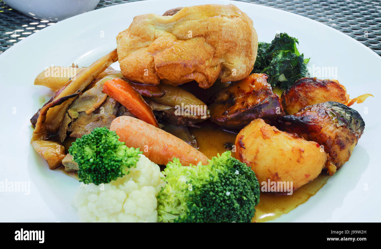Traditional English Sunday lunch food of Yorkshire pudding, slices of meat, roast potatoes, carrots, broccoli, cauliflower, - Stock Image