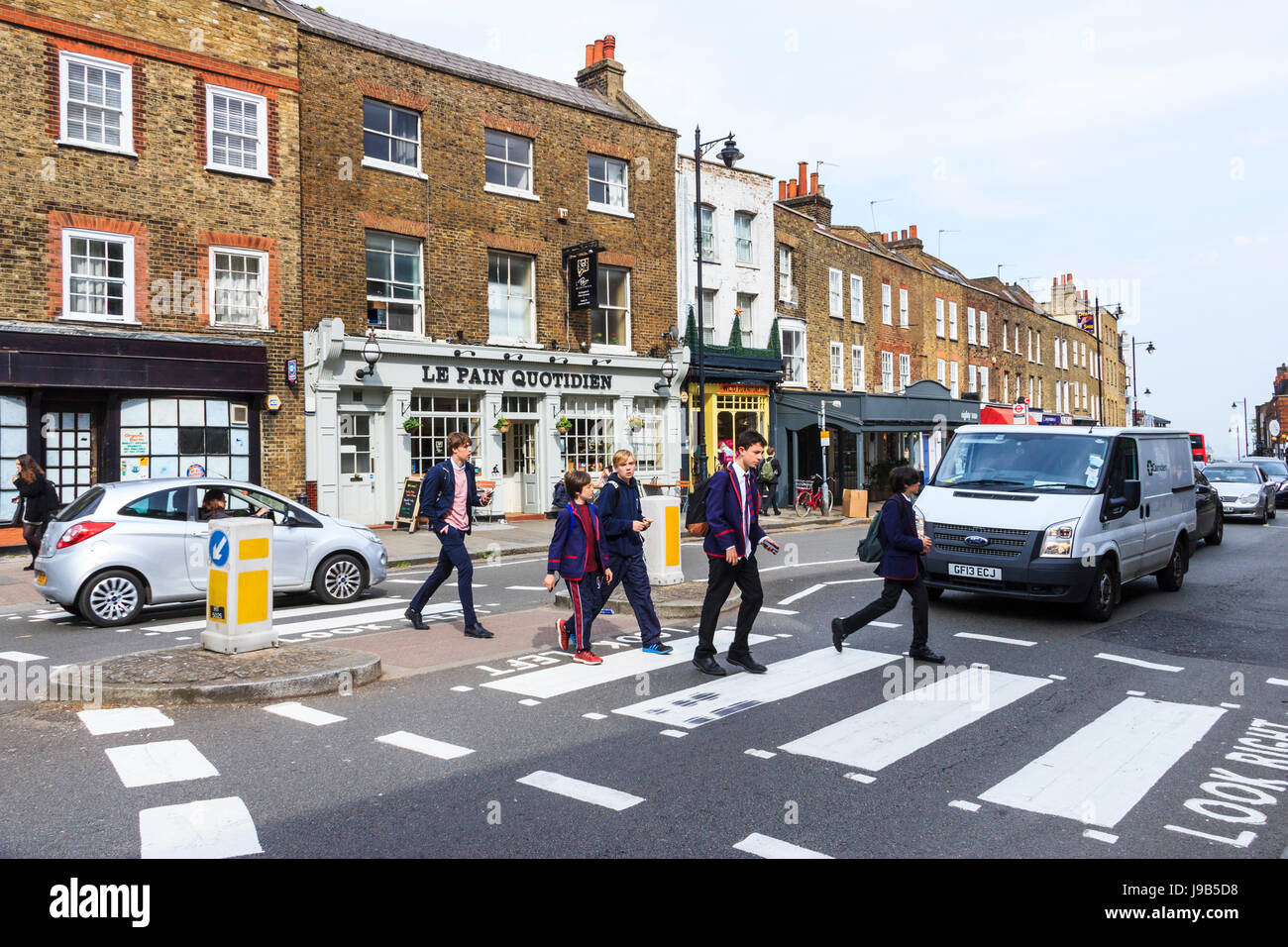 Schoolchildren crossing the road on a zebra pedestrian crossing in Highgate Village, London, UK - Stock Image