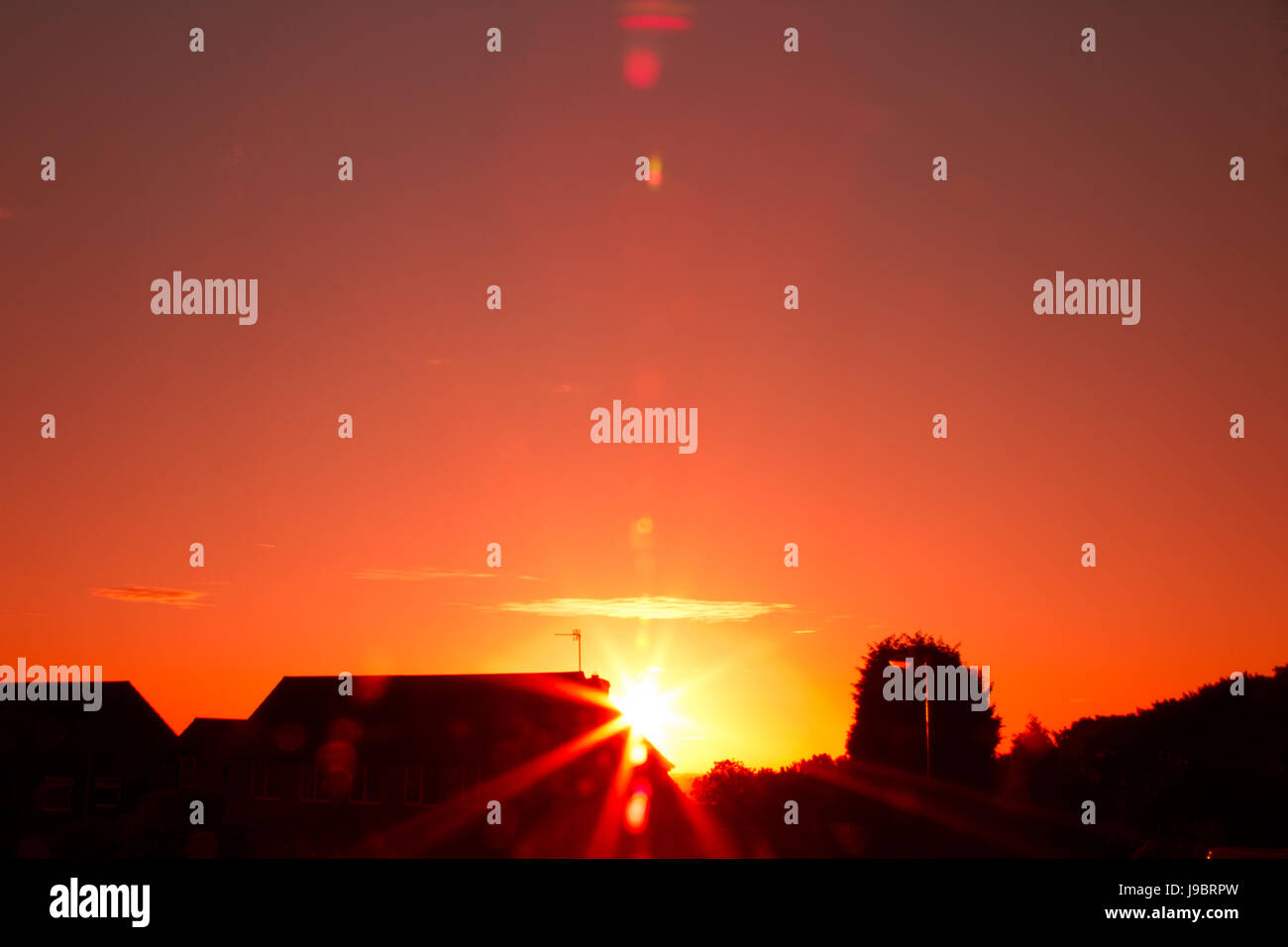 Red Sunset on an almost cloudless sky, with sun flair on the lens creating a warm feel. - Stock Image