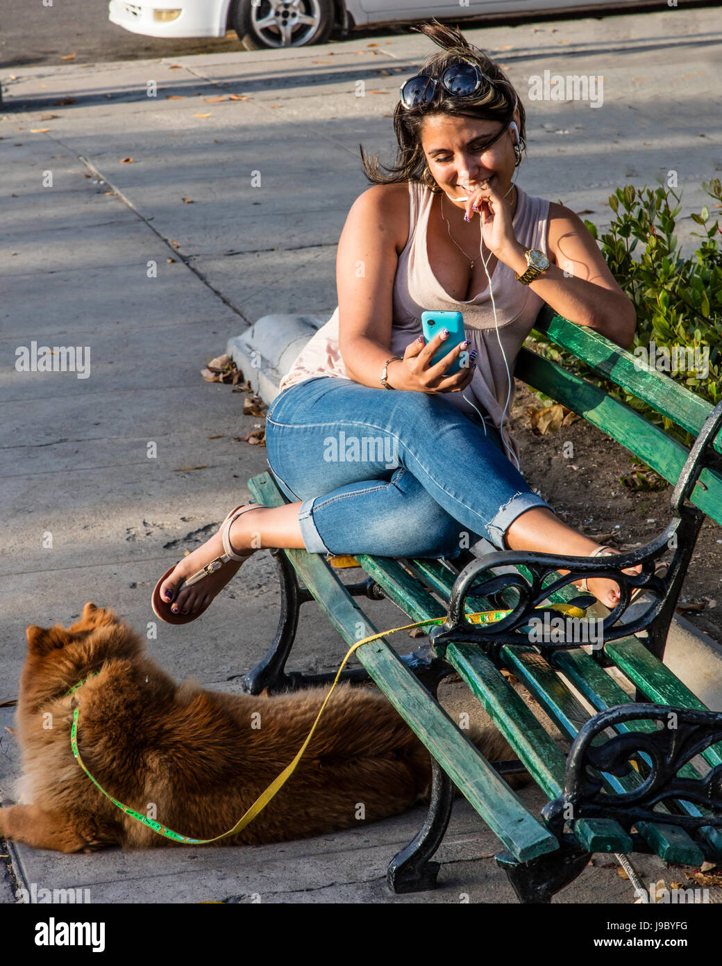 A Cuban woman enjoys talking on her cell phone in the PARQUE JOSE MARTI - CIENFUEGOS, CUBA - Stock Image