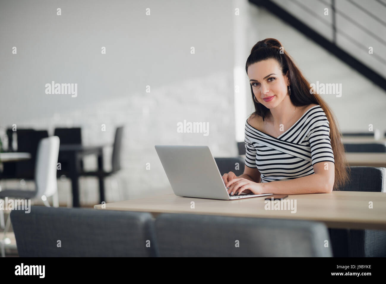 Charming female owner of business calling to manager supervising work of employee sitting in cafe interior, businesswoman - Stock Image