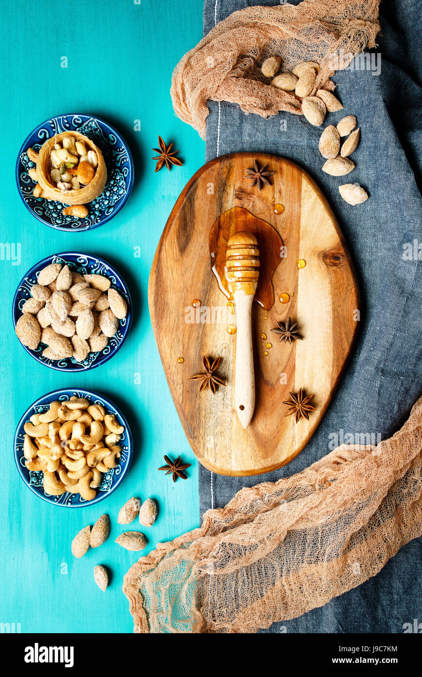 Honey dessert, nuts and honey on a rustic table, top view - Stock Image
