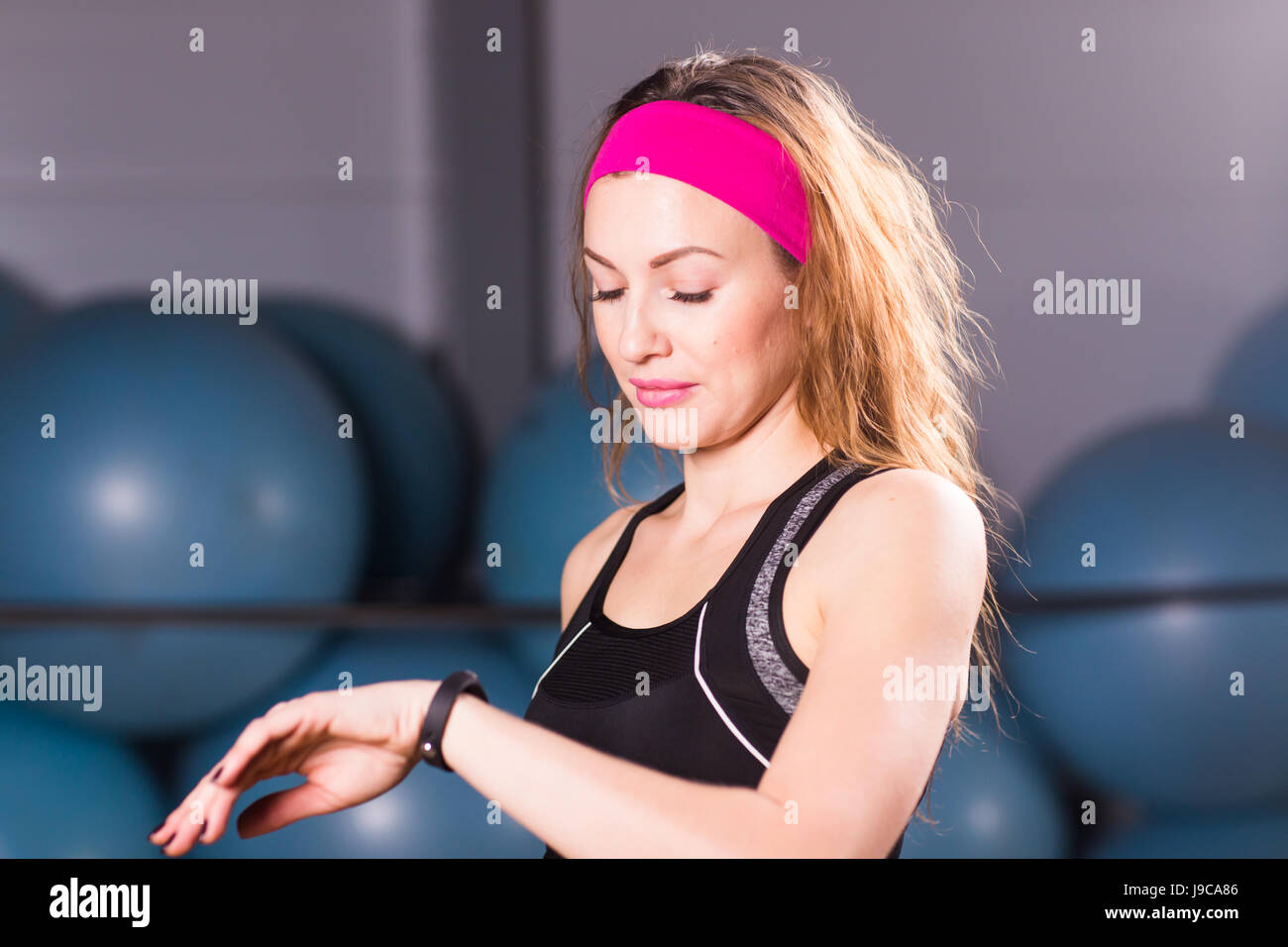 Young woman with fitness tracker and smartphone in gym - Stock Image