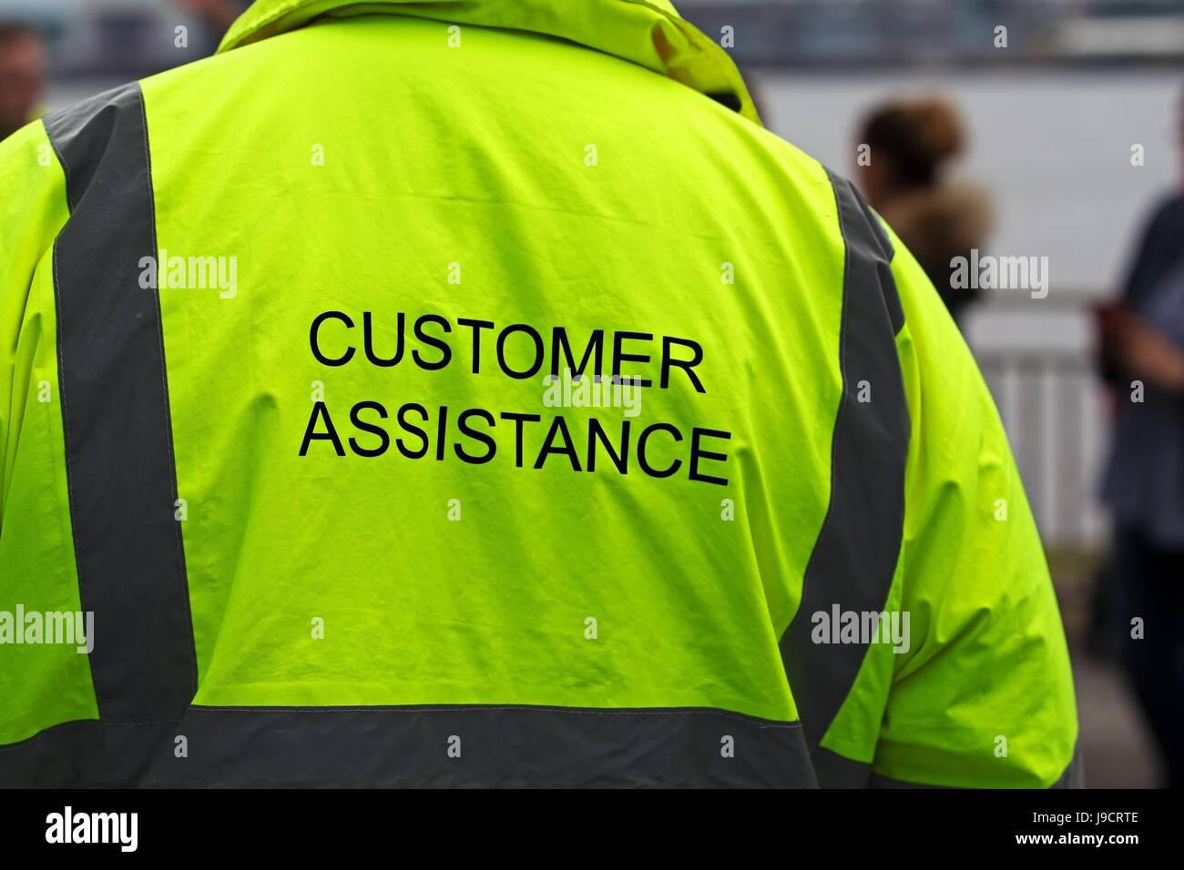 Man in hi-viz customer assistance jacket at an outdoor event Stock Photo