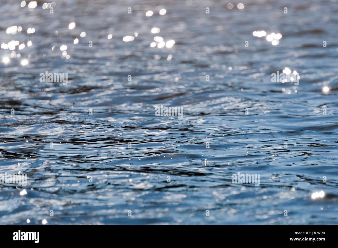 Water with bokeh background. Water surface with waves glittering in the sun - Stock Image