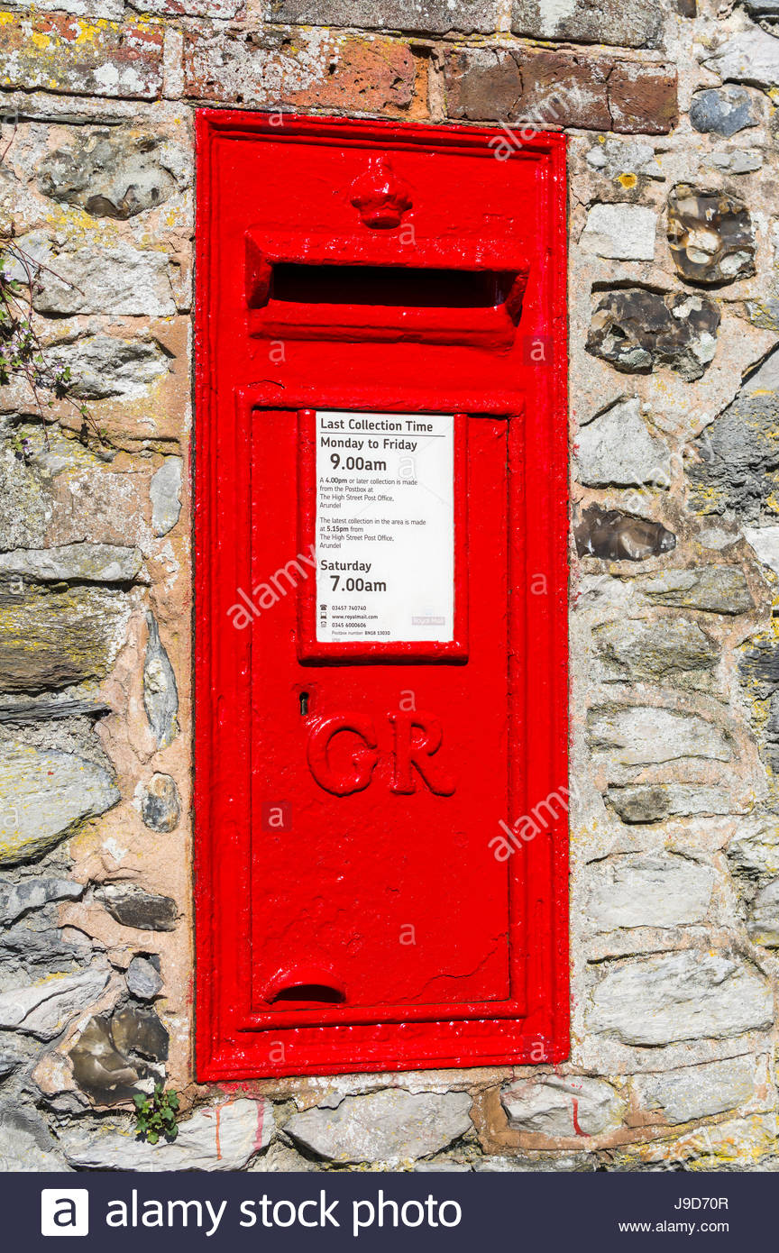 Red rectangular postbox mounted in a wall in the UK. - Stock Image