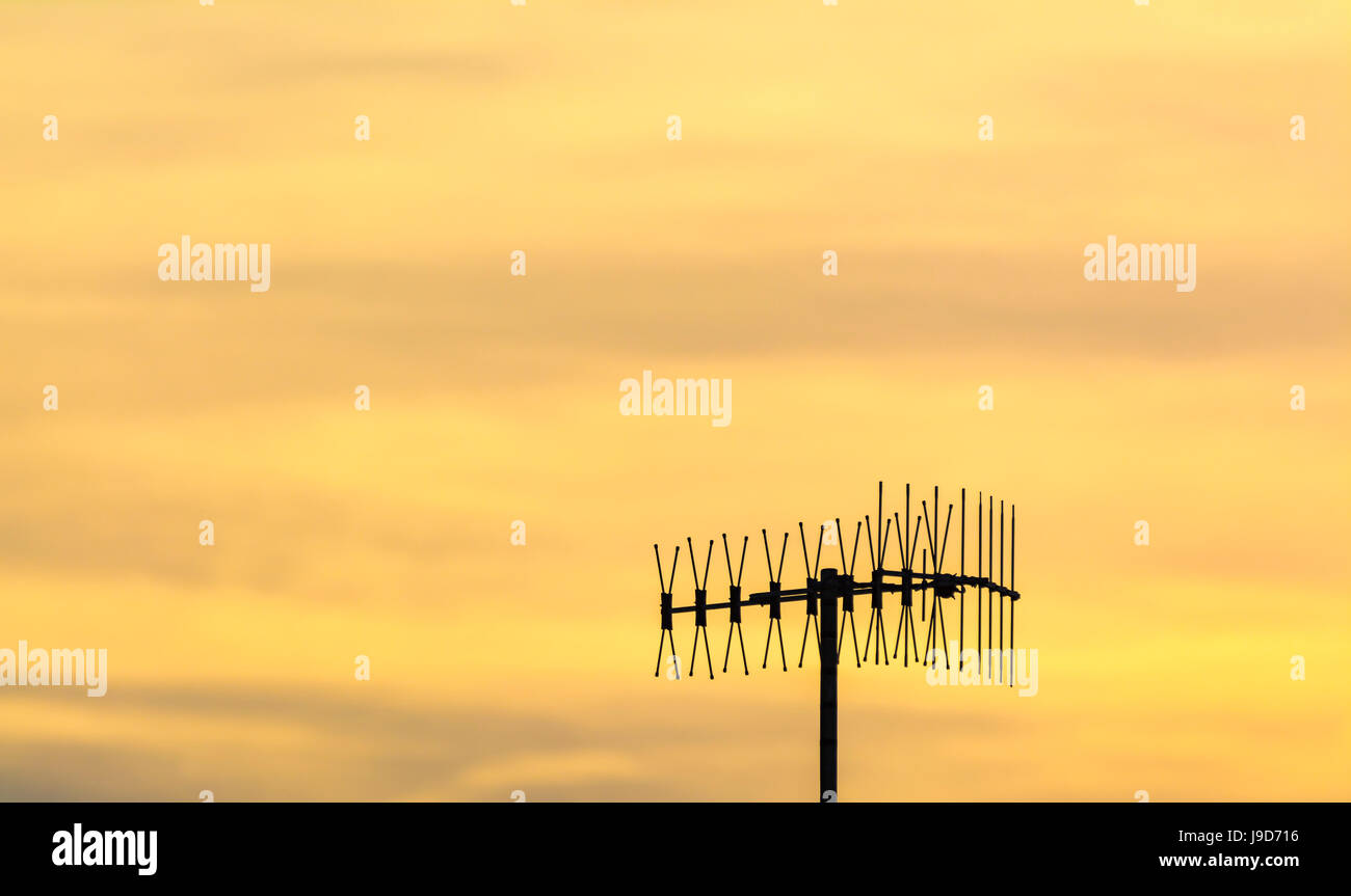 TV aerial against orange late evening sky. - Stock Image