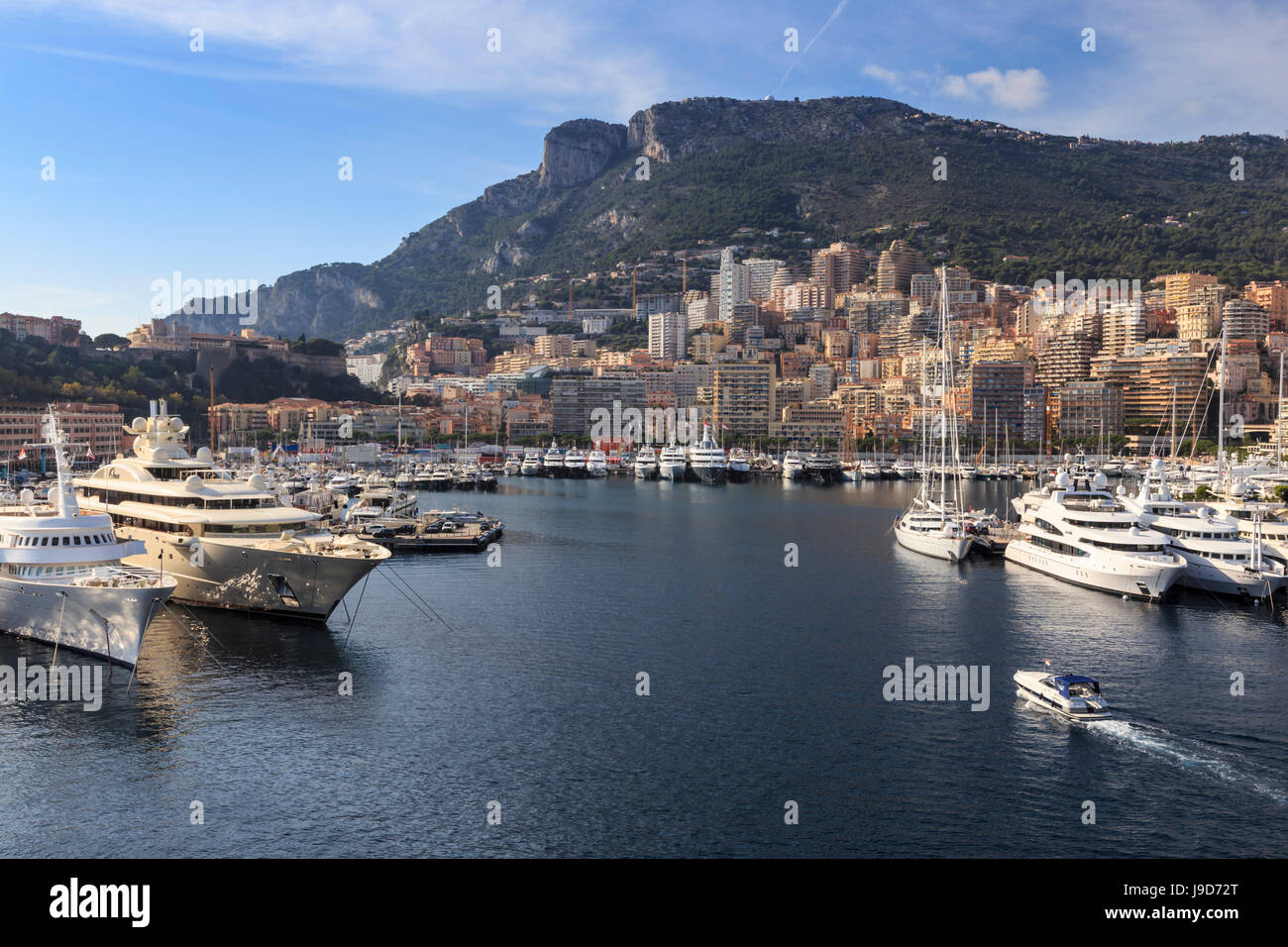 Pastel hues of the glamorous harbour of Monaco (Port Hercules) with many yachts, viewed from the sea, Monte Carlo, - Stock Image