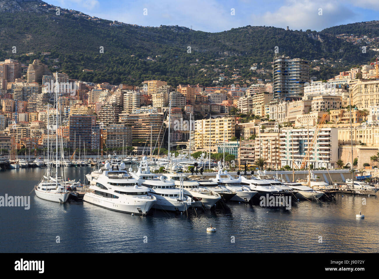 Pastel hues of the glamorous harbour of Monaco (Port Hercules) with many yachts, view from the sea, Monte Carlo, - Stock Image