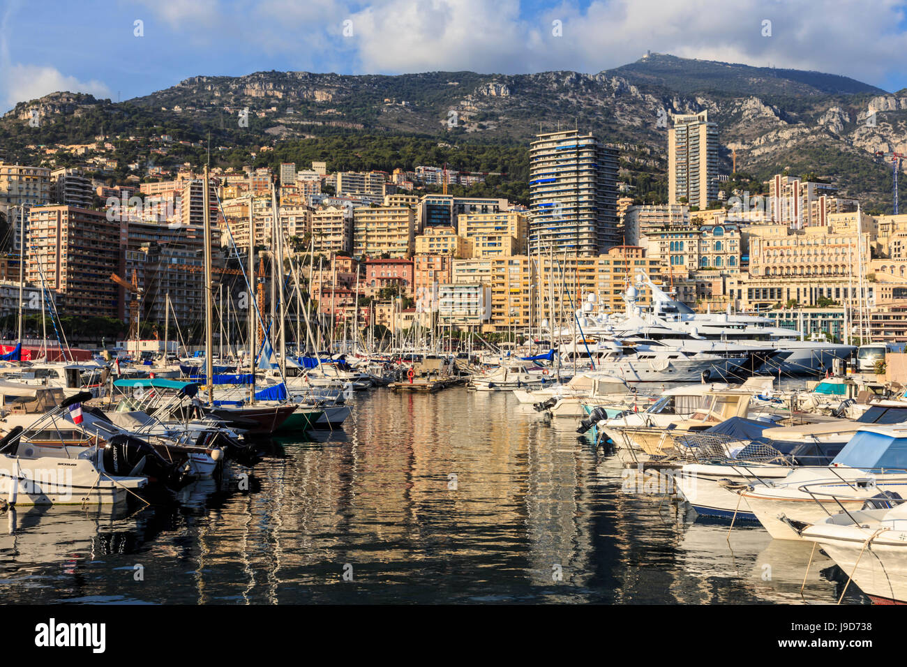 Vivid hues of the glamorous harbour of Monaco (Port Hercules) with many yachts and reflections, Monte Carlo, Monaco, - Stock Image