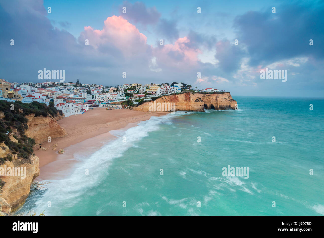 View of Carvoeiro village surrounded by sandy beach and turquoise sea at sunset, Lagoa Municipality, Algarve, Portugal, Stock Photo