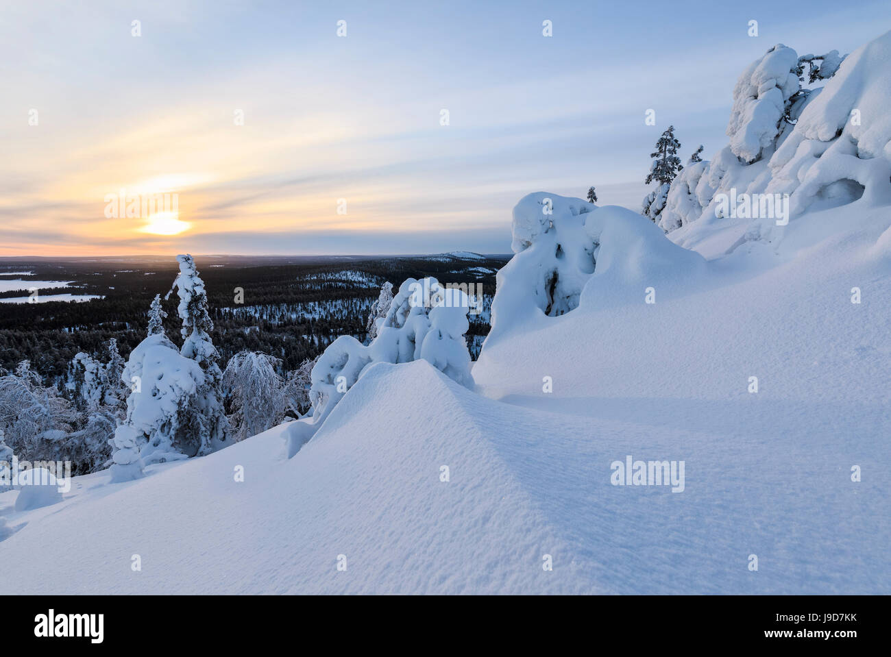 The sun frames the snowy landscape and woods in the cold arctic winter, Ruka, Kuusamo, Ostrobothnia region, Lapland, - Stock Image