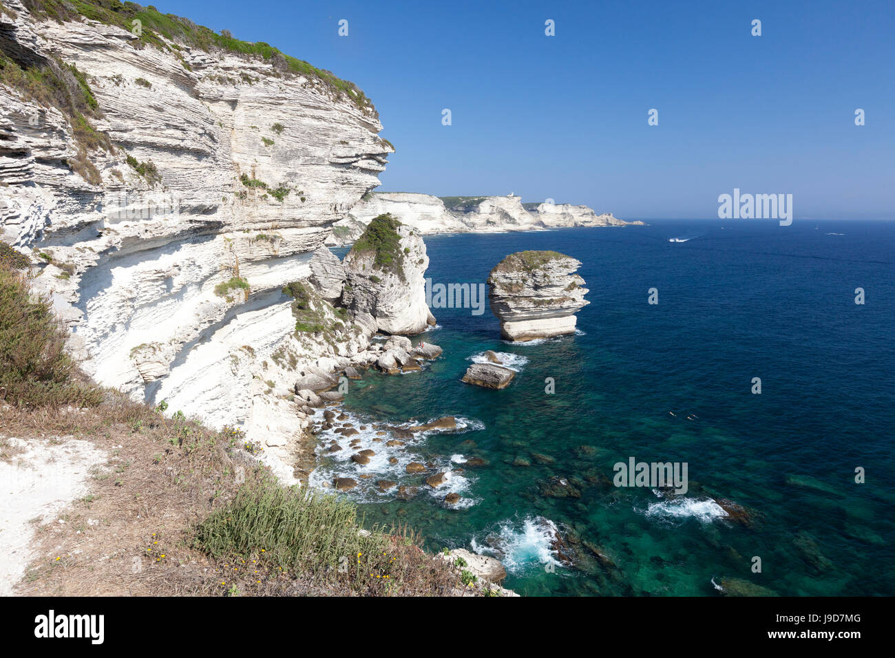 Sun shines on the white limestone cliffs framed by the turquoise sea, Bonifacio, Corsica, France, Mediterranean, Stock Photo
