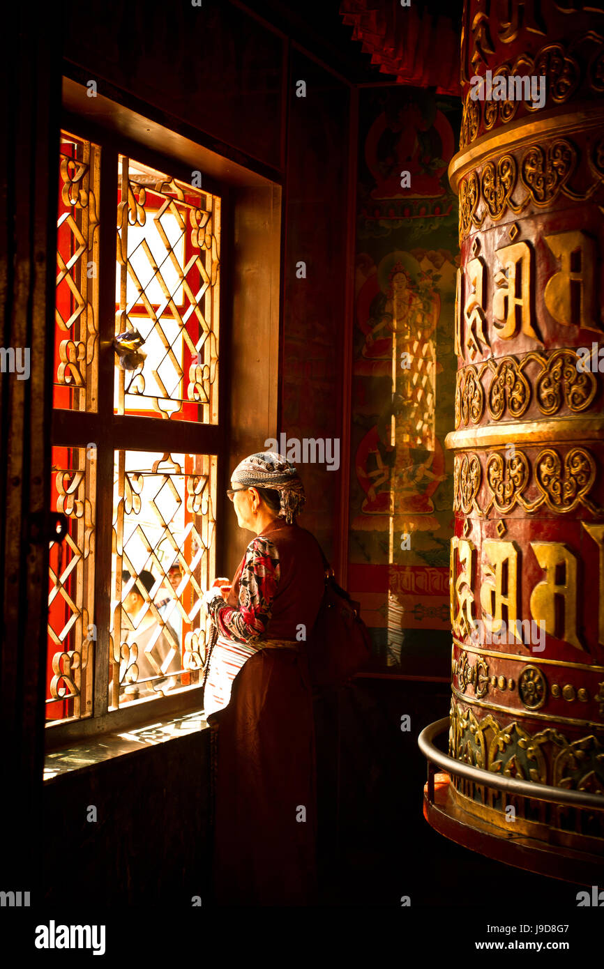 A Tibetan woman stands next to a large prayer wheel of the temple of Boudhanath Stupa, Kathmandu, Nepal, Asia - Stock Image