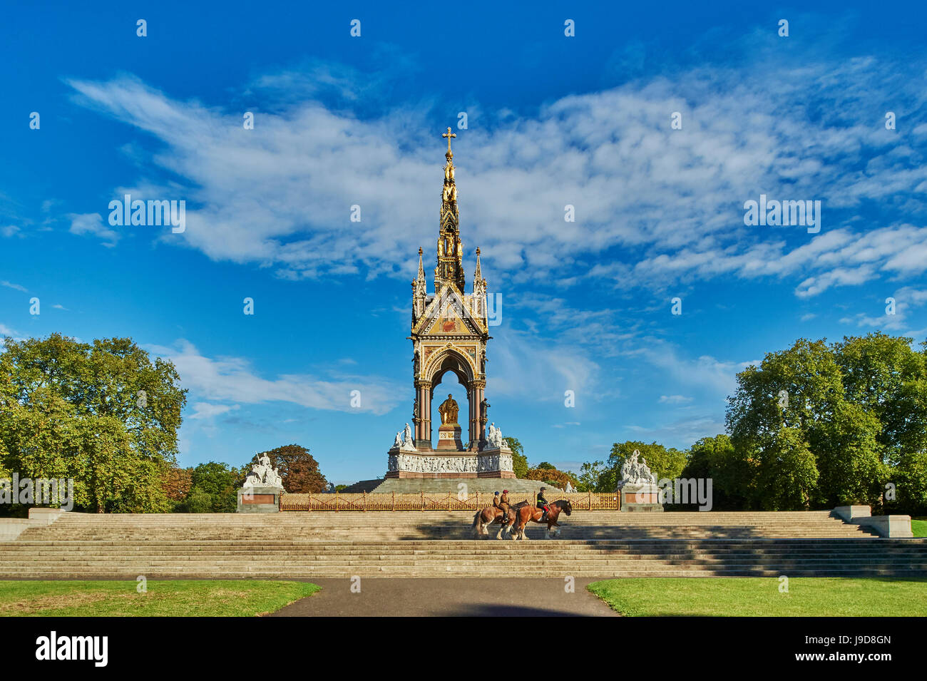 Three heavy horses are ridden past The Albert Memorial, Kensington Gardens, Hyde Park, London, England, United Kingdom, - Stock Image