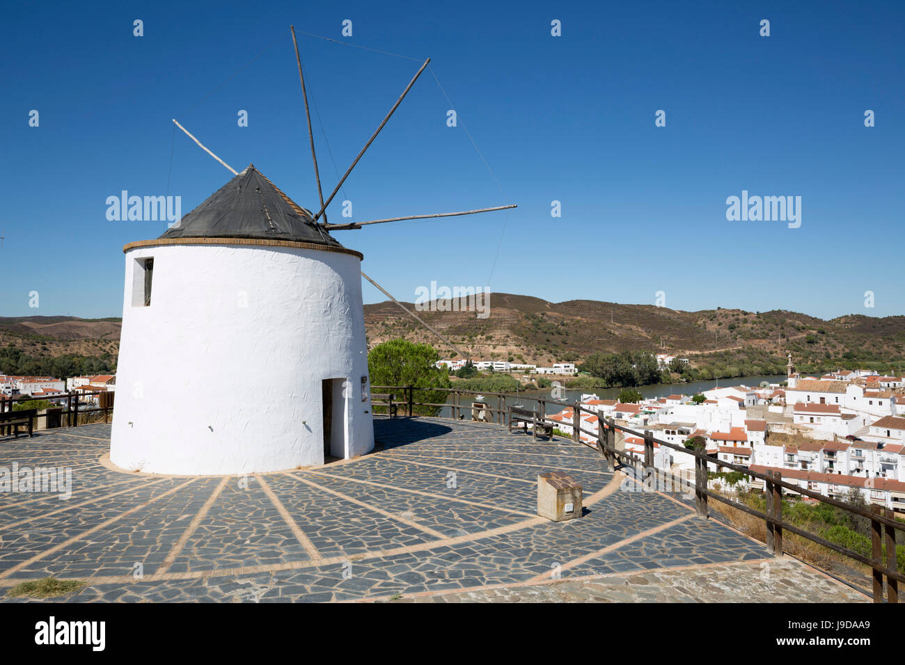 Windmill above village and Rio Guadiana river with view to Portugal, Sanlucar de Guadiana, Huelva Province, Andalucia, - Stock Image