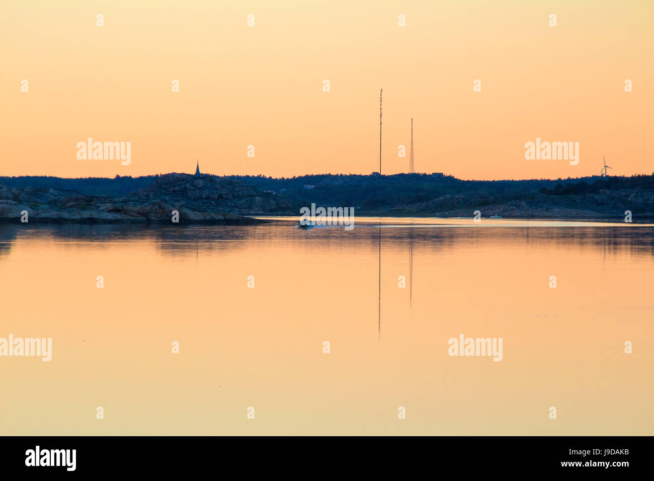 Boat driving in the sunset over mirror clear ocean - Stock Image