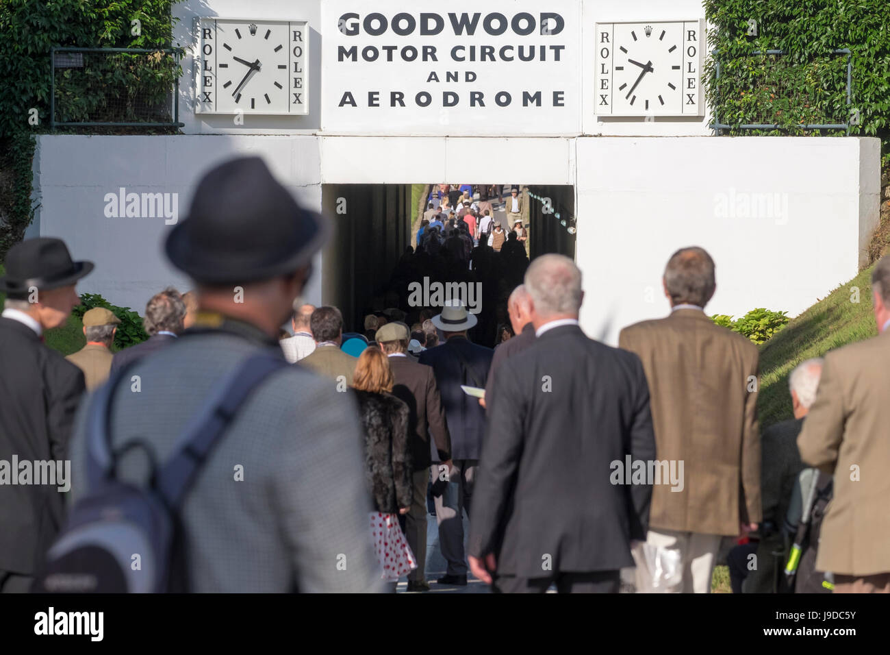 Crowd of people squeezing squashing together whilst walking through the tunnel at goodwood motor racing circuit - Stock Image