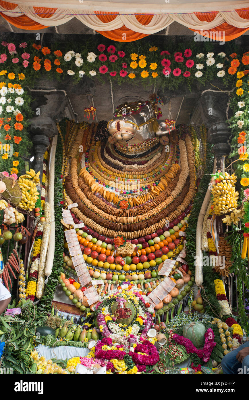 A Statue Of The Hindu Deity Nandi Is Decorated With Items Of Food
