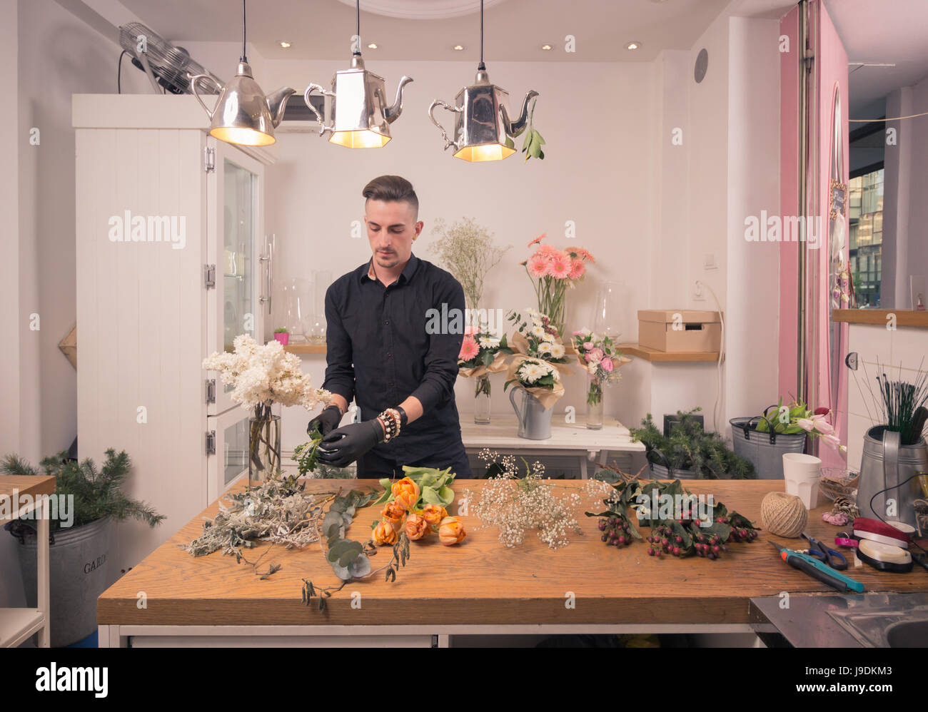 one young adult man, florist, arranging flowers, flower shop indoors - Stock Image