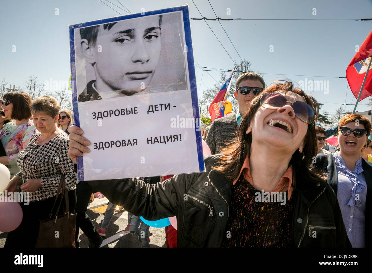 A woman holds a portrait of young Vladimir Putin with the inscription 'Healthy children - healthy nation!' - Stock Image