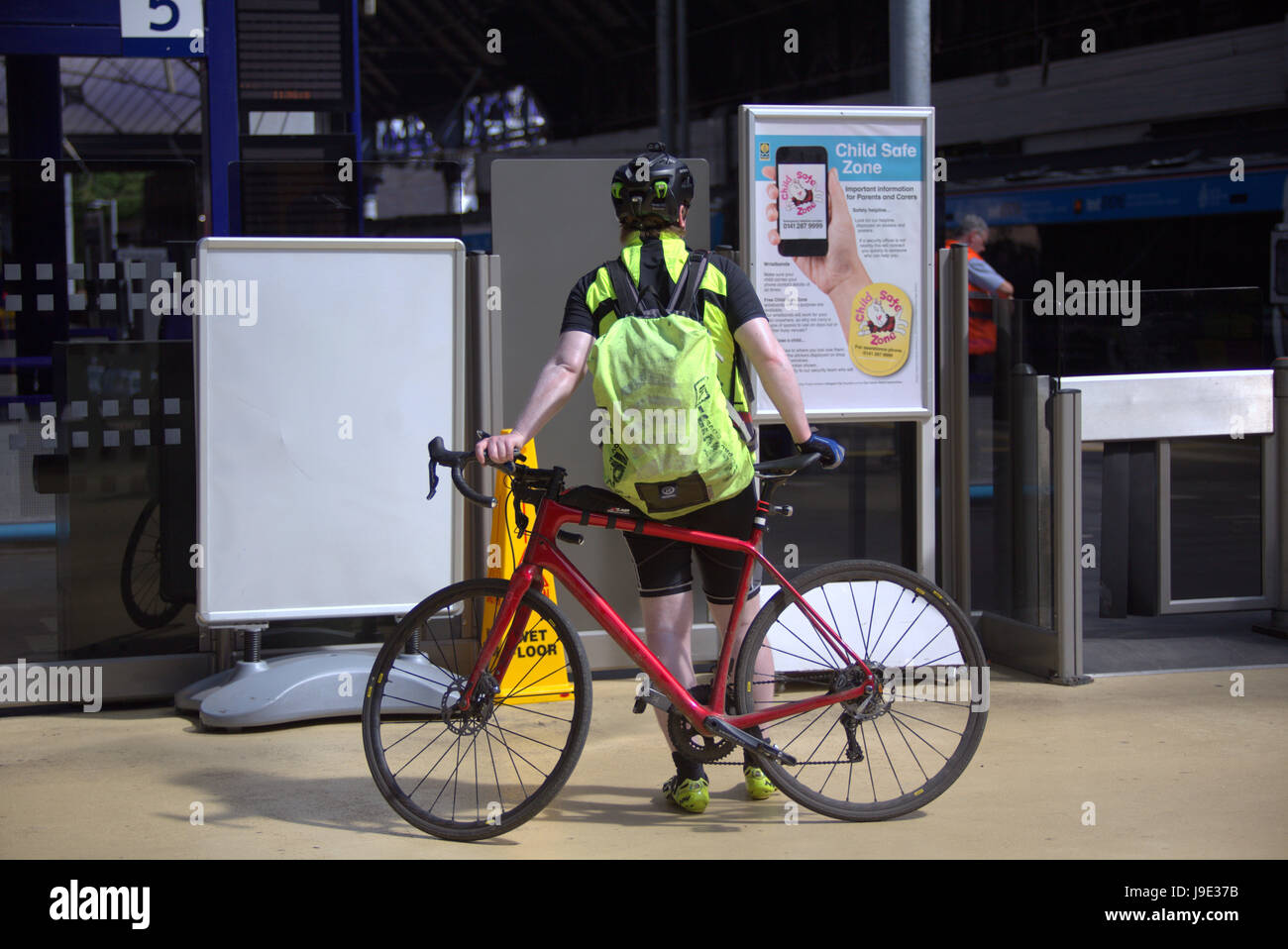 cyclist at queen street station railway under the Gaelic  sign scotrail - Stock Image