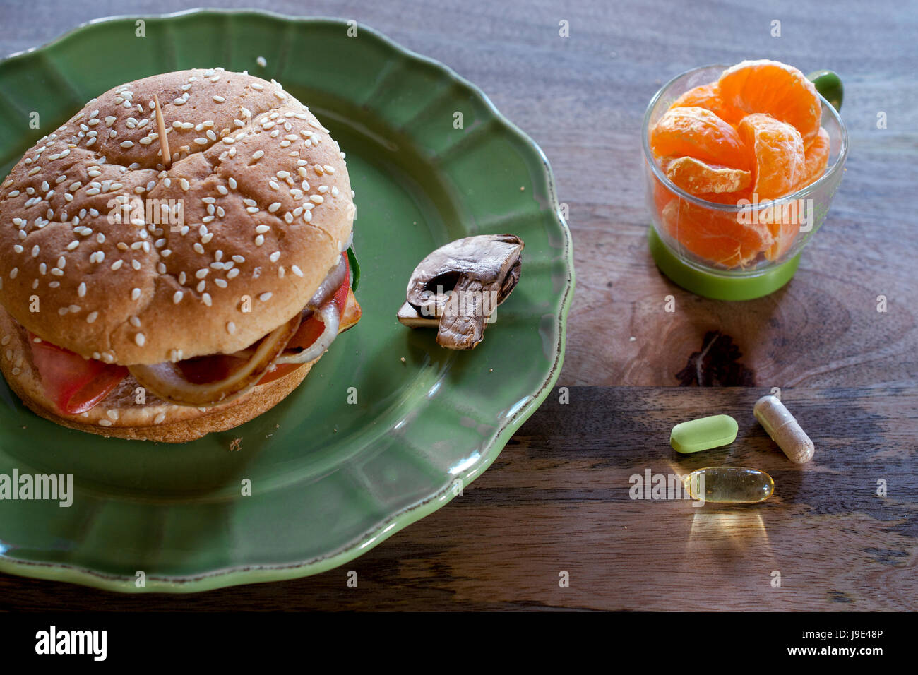 Vegan hamburger on green plate, viewed from above, served with mushroom and tangerine slices, on wooden table, and - Stock Image