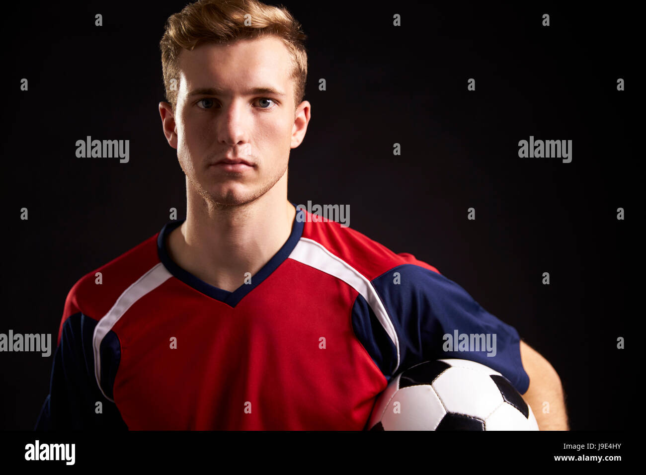 Portrait Of Professional Soccer Player With Ball In Studio - Stock Image