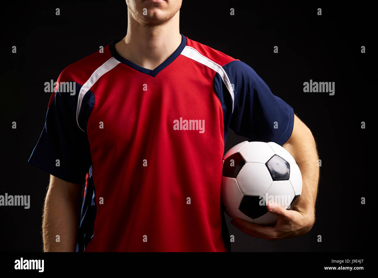 Close Up Of Professional Soccer Player With Ball In Studio - Stock Image