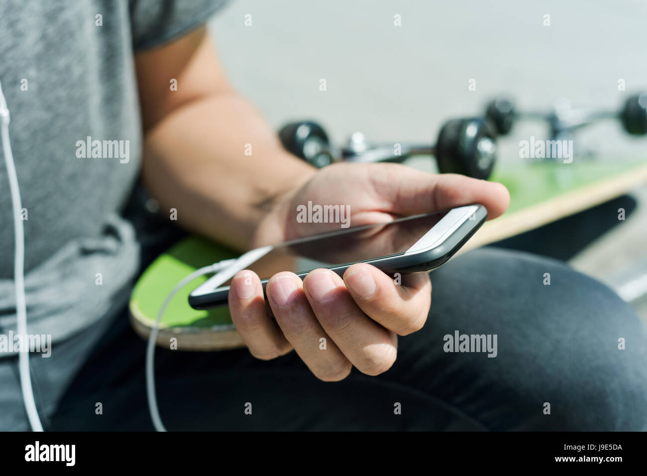 closeup of a young caucasian man outdoors with a skateboard on his lap using his smartphone with earphones plugged - Stock Image
