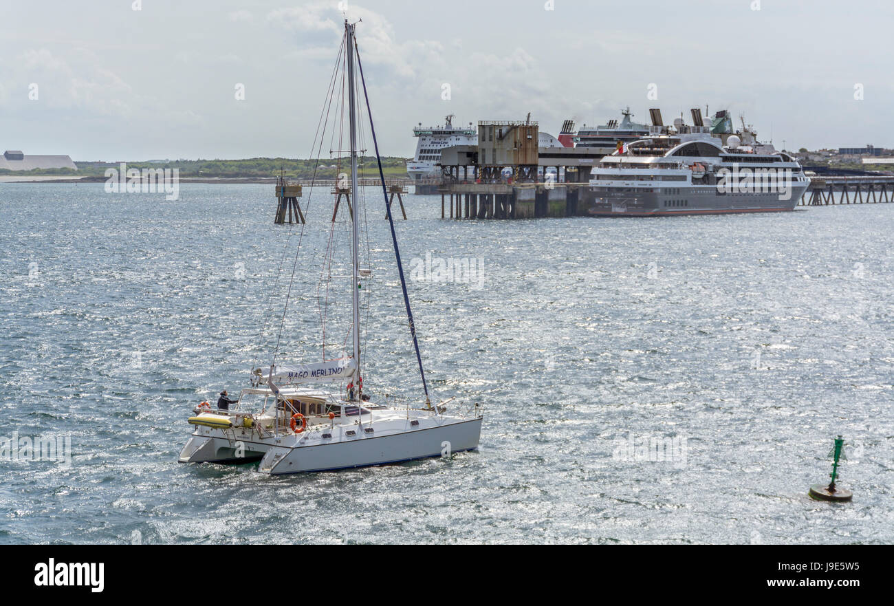 A catamaran passes the docked cruise ship and ferries at Holyhead on Anglesey. - Stock Image