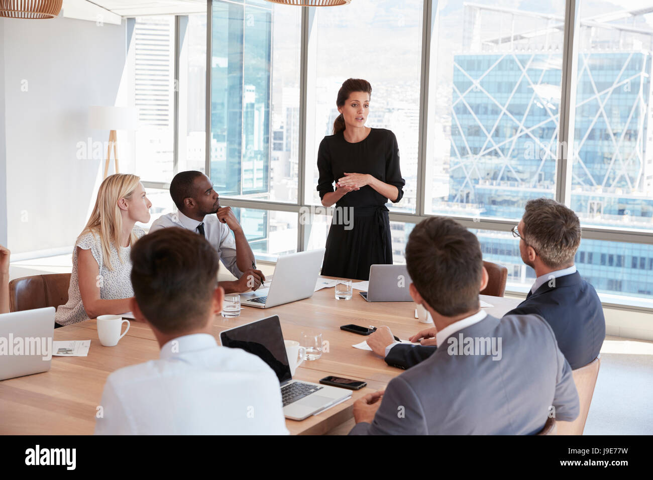 Businesswoman Stands To Address Meeting Around Board Table - Stock Image