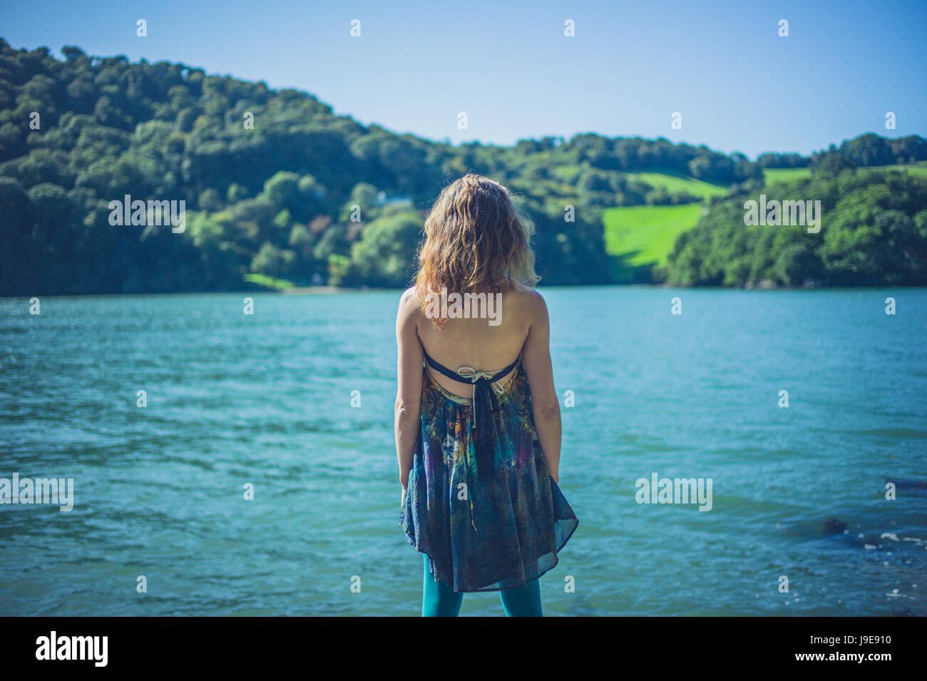 A young woman is standing by the water on a sunny summer's day - Stock Image