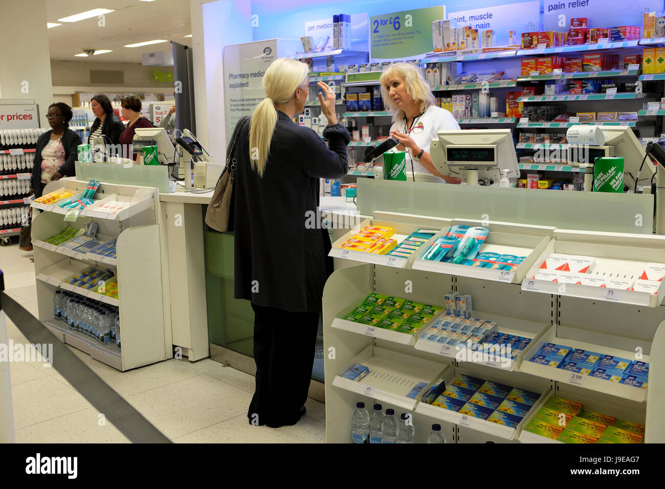 A woman customer talking to a shop assistant at the checkout counter of a Boots the Chemist pharmacy drugs store - Stock Image