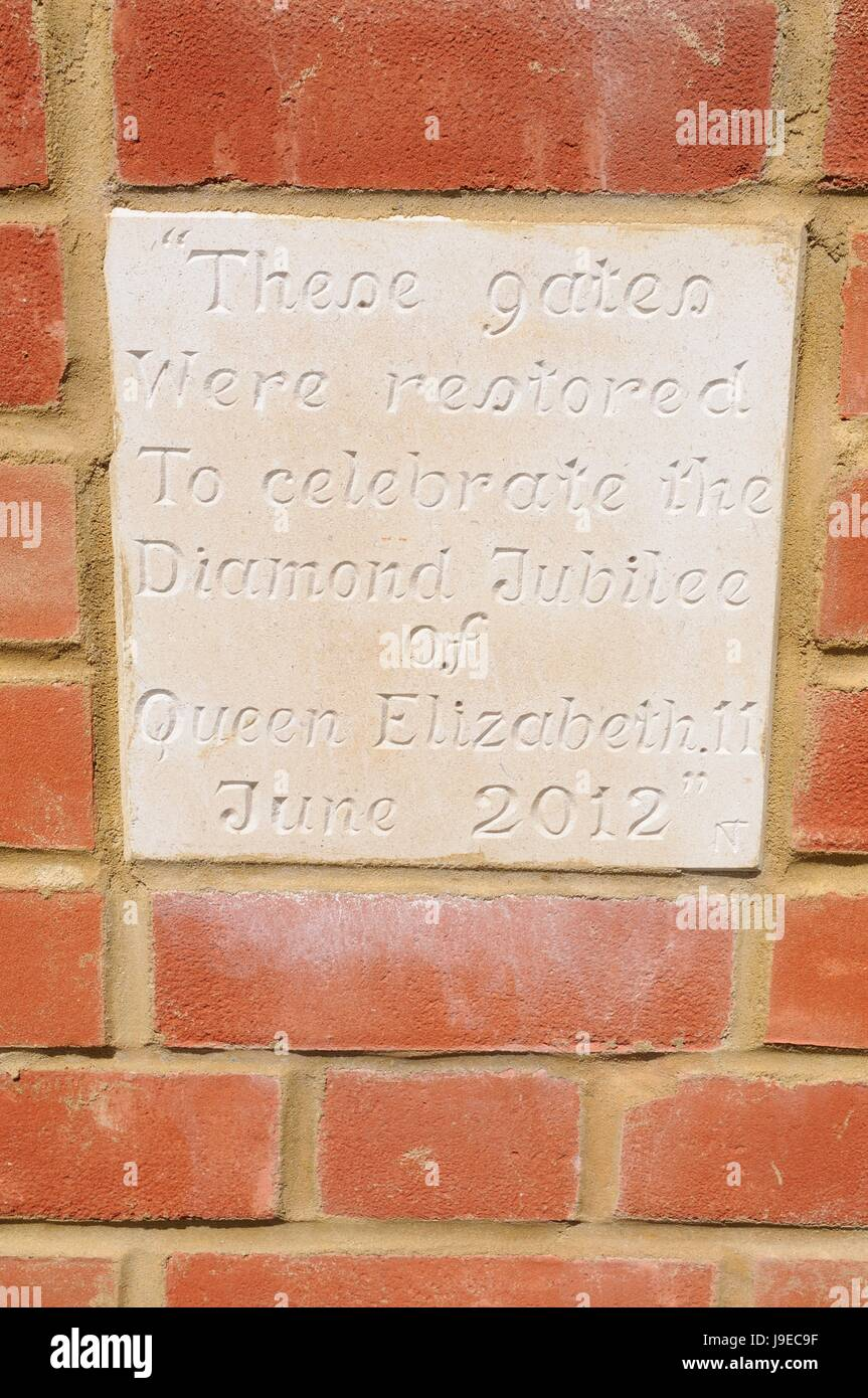 Stone plaque on gateway at St Mary Church, North Marston, Buckinghamshire.  the gates were restored to celebrate - Stock Image
