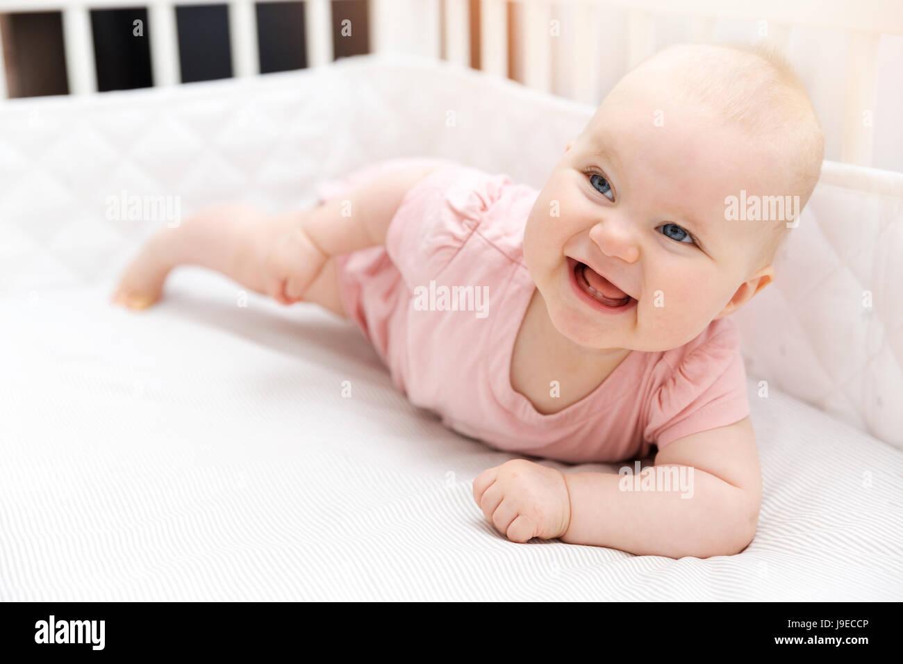 happy smiling baby girl in crib Stock Photo